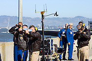 Blue Angels support crew reflect sunlight and shine an electronic beacon at Blue Angels jets in flight to assist them in navigating the Fleet Week performance in San Francisco while the Blue Angels announcer stands at attention in the background.