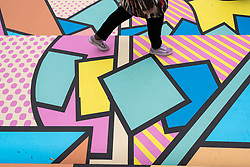 "© Licensed to London News Pictures. 07/04/2018. LONDON, UK.  A visitor walks across the colourful entrance mural by graphic designer artist Supermundane outside ""Sense of Space"", an art pop-up which opened to the public in Broadgate.  Comprising four rooms to challenge the visitor's sensory perceptions through art, the installation is open until 18 May.  Photo credit: Stephen Chung/LNP"