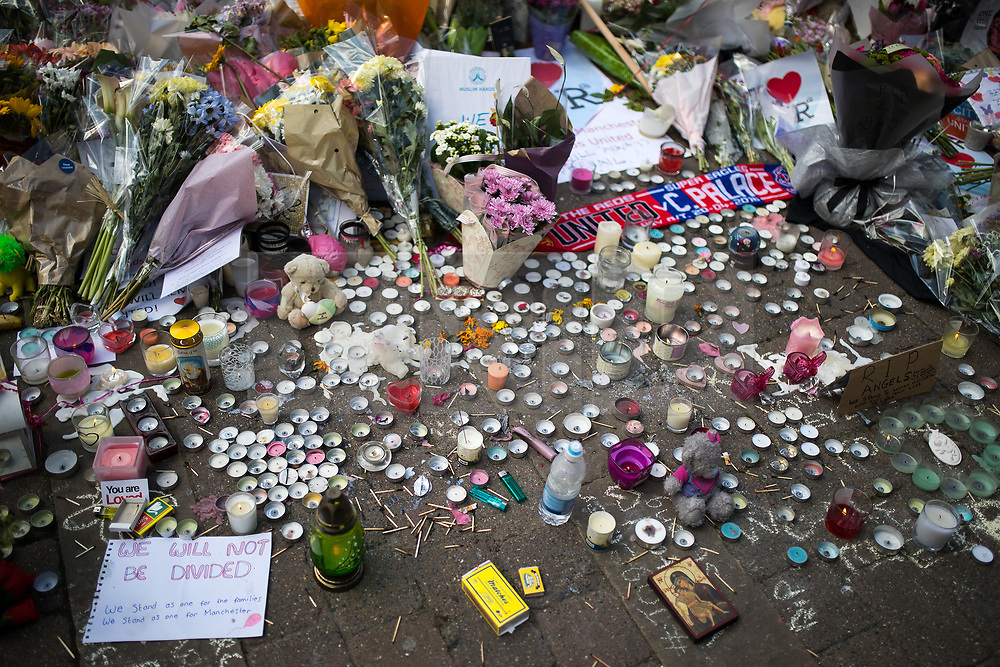 © Licensed to London News Pictures . 25/05/2017 . Manchester , UK . People gather round flowers and tributes spread across the width of St Ann's Square in Manchester City Centre , following a terrorist attack at an Ariana Grande concert at Manchester Arena that killed twenty two people . Photo credit : Joel Goodman/LNP