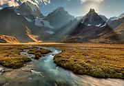 Sun sets behind Jirishanca, Yerupaja on left, river flows into Carhuacocha lake, Cordillera Huayhuash, Andes mountains, northern Peru
