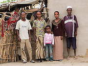 Shekur Mohammaed( right), 60, and his family outside their house in Zwei, Ethiopia. Left to right: Muhidin, 25, Fatuma Delbo, 40, Elefelesh, 9, eldest daughter and Shekur Mohammaed...Shekur and his family are beginning to really suffer as their maize crops have failed due to a lack of rain. SEDA, who work with Send a Cow, are about to start work with them to teach them some basic farming techniques to diversify their crop range and improve their yield, even when the rains don't come...The first step is under way and Shekur has paid a specialist well digger to start digging a well.