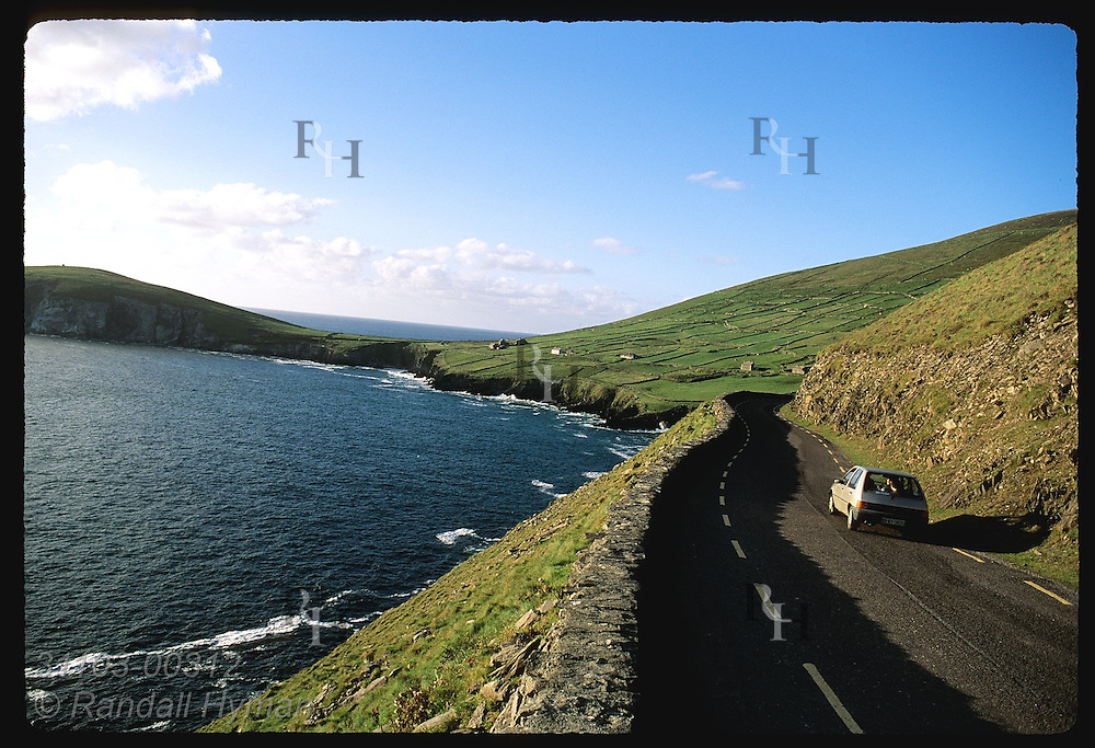Car drives along Slea Head overlooking Dingle Bay with Dunmore Head in distance; Dingle Peninsula, Ireland.