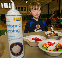 """William Vashaw goes for everything """"chocolate"""" on his ice cream sundae during Laconia's Summer Programs final day at the Laconia Community Center on Wednesday afternoon.  (Karen Bobotas/for the Laconia Daily Sun)"""