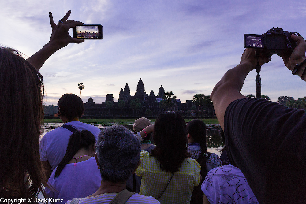 "02 JULY 2013 - ANGKOR WAT, SIEM REAP, SIEM REAP, CAMBODIA:  A tourist uses his smart phone to photograph the Angkor Wat sunrise. Angkor Wat is the largest temple complex in the world. The temple was built by the Khmer King Suryavarman II in the early 12th century in Yasodharapura (present-day Angkor), the capital of the Khmer Empire, as his state temple and eventual mausoleum. Angkor Wat was dedicated to Vishnu. It is the best-preserved temple at the site, and has remained a religious centre since its foundation – first Hindu, then Buddhist. The temple is at the top of the high classical style of Khmer architecture. It is a symbol of Cambodia, appearing on the national flag, and it is the country's prime attraction for visitors. The temple is admired for the architecture, the extensive bas-reliefs, and for the numerous devatas adorning its walls. The modern name, Angkor Wat, means ""Temple City"" or ""City of Temples"" in Khmer; Angkor, meaning ""city"" or ""capital city"", is a vernacular form of the word nokor, which comes from the Sanskrit word nagara. Wat is the Khmer word for ""temple grounds"", derived from the Pali word ""vatta."" Prior to this time the temple was known as Preah Pisnulok, after the posthumous title of its founder. It is also the name of complex of temples, which includes Bayon and Preah Khan, in the vicinity. It is by far the most visited tourist attraction in Cambodia. More than half of all tourists to Cambodia visit Angkor.         PHOTO BY JACK KURTZ"