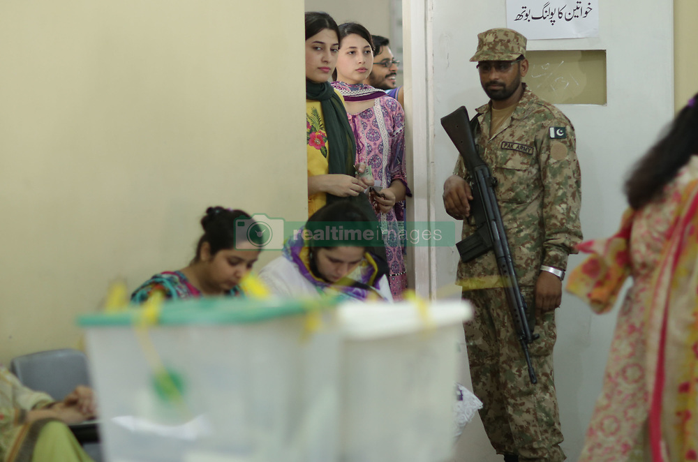July 25, 2018 - Lahore, Punjab, Pakistan - Voters casts their vote while Military officials and polling staff watch at a polling station during Pakistan's general election in Lahore on July 25, 2018. Pakistanis are voting today in a closely fought election that will determine the course of the nuclear-armed nation central to U.S. anti-terrorism efforts and Chinas global infrastructure ambitions. Pakistanis voted July 25 in elections that could propel former World Cup cricketer Imran Khan to power, as security fears intensified with a voting-day blast that killed at least 28 after a campaign marred by claims of military interference. Polling began at 8AM and will conclude, without any break, at 6PM across the country's 85,307 polling stations, of which 17,007 have been declared highly sensitive. (Credit Image: © Rana Sajid Hussain/Pacific Press via ZUMA Wire)