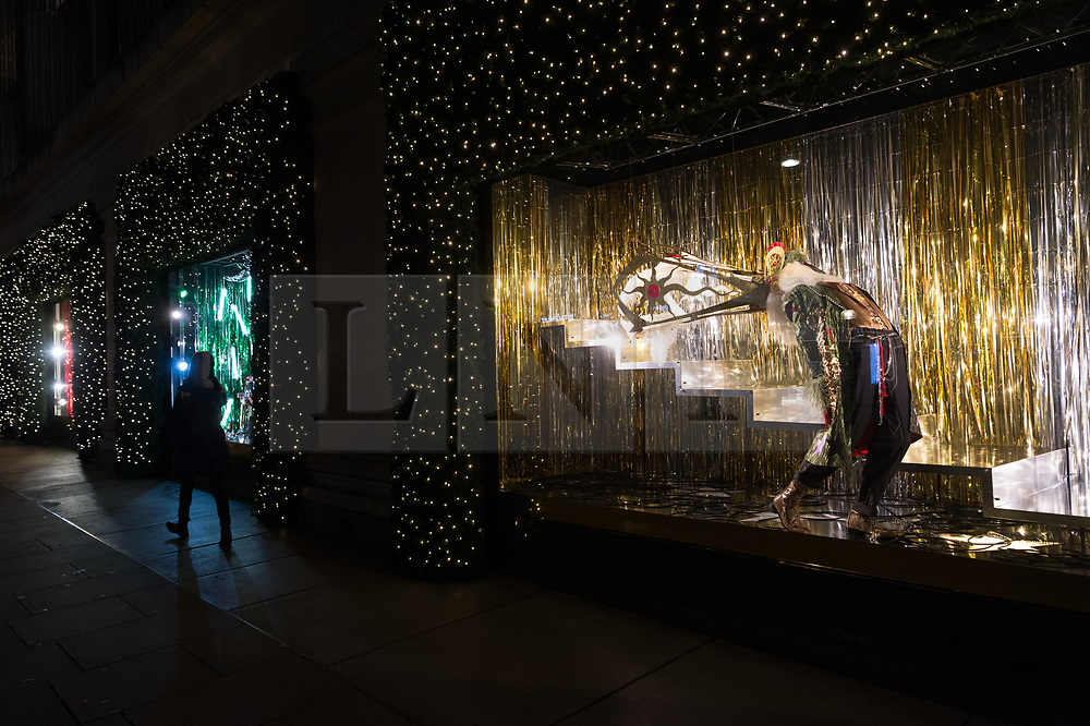 © Licensed to London News Pictures. 18/10/2018. London, UK. A women walk past a Selfridges department store Christmas festive window display with a 'Selfridges Rocks Santa' theme. It is the first department store in the world to unveil Christmas windows. Photo credit: Ray Tang/LNP