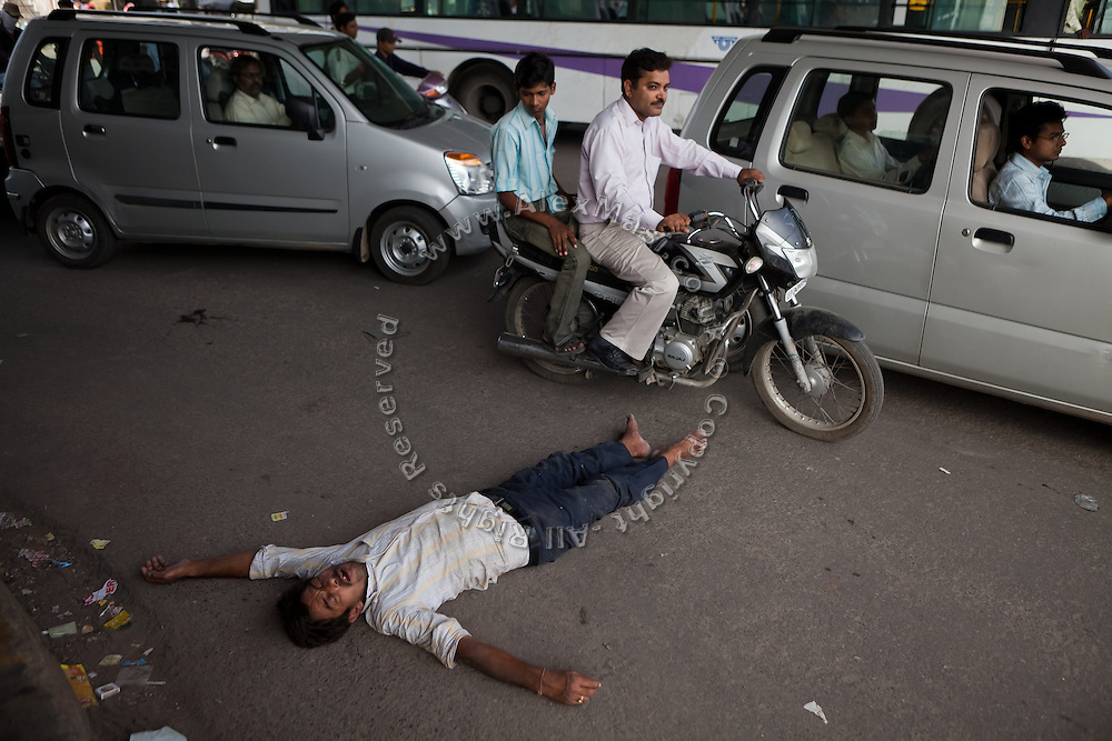 A man is lying, supposedly drunk, in the middle of a congested junction. The Taj Mahal has been struggling to keep in shape also because of the high levels of pollution in the city, mainly caused by congested roads and high levels of traffic, vehicles and an increasing population, in Agra.