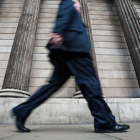 London, UK - 5 September 2014: A businessman walks in front of the columns of the Bank of England in the City of London