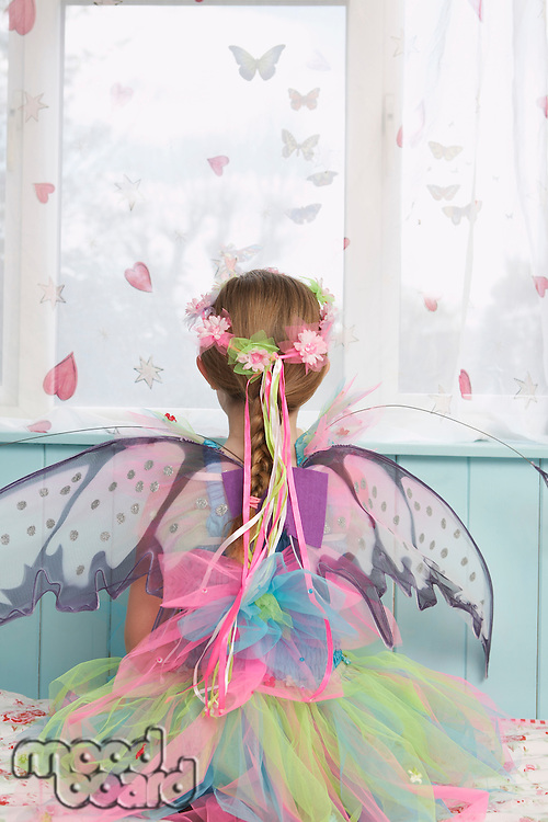 Young girl (5-6) wearing fairy costume looking through window back view