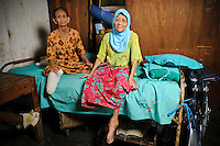 Ibu Sani (l) and Ibu Mida (r) at the Jongaya leprosy settlement, Makassar, Sulawesi, Indonesia. Ibu Sani (left), 70, has been in Jongaya for over 30 years.  She is originally from Bone in Sulawesi where she lived with her family, but when she was 40 years old she discovered she was infected with leprosy and moved to Jongaya.  She lost her leg 20 years ago as a result of the disease.  She now lives with Ibu Mida and Ibu Nuria at a shelter for older people.  Her family from Bone still come and visit her at the shelter. Ibu Mida (right), 50, is originally from Gowa and has been at the Jongaya settlement for 'A long time'.