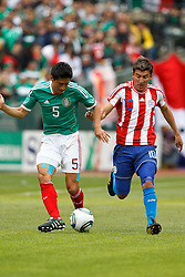 March 26, 2011; Oakland, CA, USA;  Mexico defender Ricardo Osorio (5) dribbles past Paraguay forward Edgar Benitez (10) during the first half at Oakland-Alameda County Coliseum. Mexico defeated Paraguay 3-1.