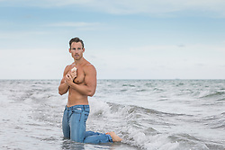 Sexy man in the ocean holding a shell to his heart
