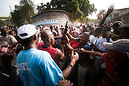 Protesters wrestled for control of a shotgun wielded by a security guard of the Haitian presidential candidate Jude Celestin's campaign office. Thousands of Haitians took to the streets of Port-au-Prince in support of Michel Martelly, another candidate who placed third in the previous day's announcement of preliminary election results..