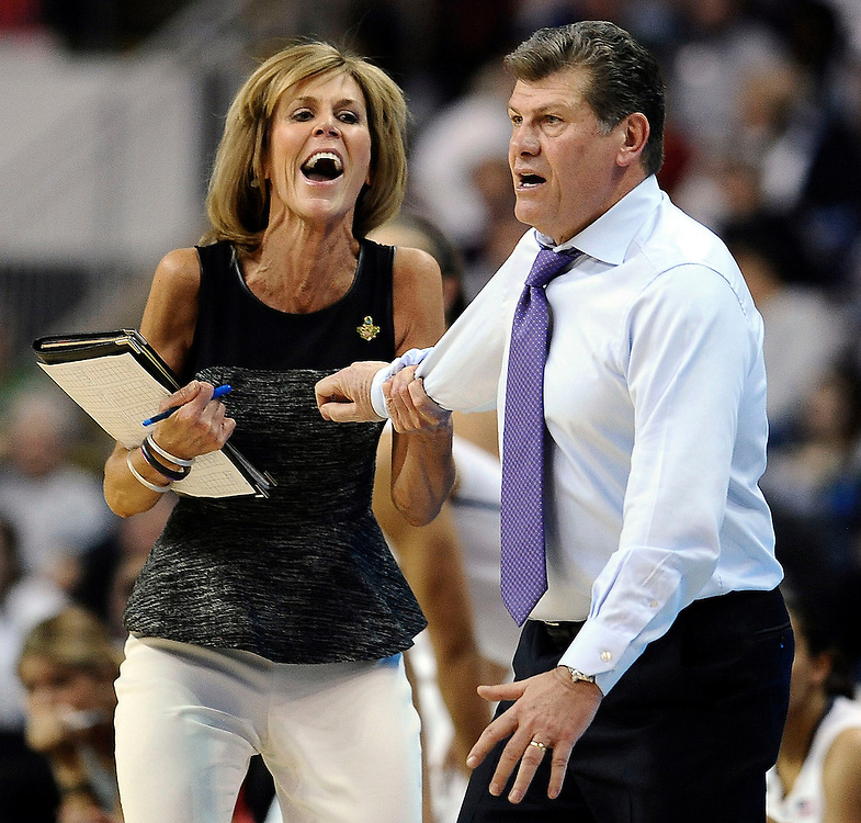 Connecticut associate head coach Chris Dailey, left, pulls back head coach Geno Auriemma, right, during the first half of a regional semifinal against Maryland in the NCAA college basketball tournament in Bridgeport, Conn., Saturday, March 30, 2013. (AP Photo/Jessica Hill)