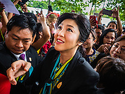05 AUGUST 2016 - BANGKOK, THAILAND: YINGLUCK SHINAWATRA walks through a mob of supporters at the Supreme Court of Thailand Friday. She appeared in court to start her legal defense. She was deposed by a military coup in 2014 and is being tried on corruption and mismanagement charges related to a price support plan for Thai rice farmers that was instituted while she was Prime Minister. More than two years after her government was deposed by a military coup, she is still a popular figure and hundreds of her supporters packed the area around the courthouse to greet her when she arrived at the Court.       PHOTO BY JACK KURTZ