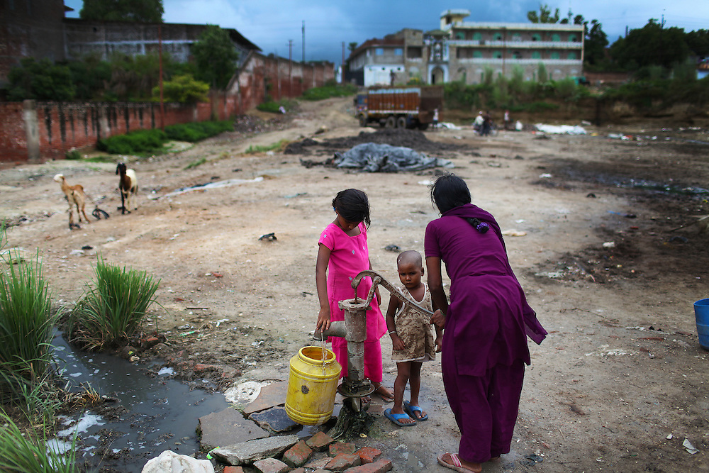 A mother gathers water from a well at a dumping site for the dicarded scraps from the tanneries. The scraps are soaked with toxic chemicals which soak into the ground and contaminate the water sources.