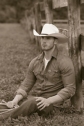 cowboy relaxing by a fence on a ranch