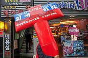Mann traegt im Zentrum der koreanischen Metropole Seoul ein gro?es Kreuz. ..Man carrying a big cross in the city center of the korean capital Seoul.