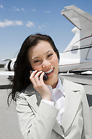 Portrait of Asian mid-adult businesswoman standing outside private jet and talking on mobile phone.
