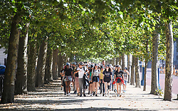 © Licensed to London News Pictures. 23/07/2018. London, UK. Tourists in summer clothing walk along The Mall in in early morning sun in central London, as the hot weather continues in the capital. Forecasters are predicting record temperatures this week. Photo credit: Ben Cawthra/LNP