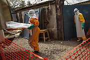 The Red Cross is undertaking safe and dignified burials in all Ebola-affected countries, ensuring that those who have died from the disease are treated with respect, while also ensuring the safety of communities. This is critical work, often performed by volunteers, and undertaken at the most dangerous time.<br /> <br /> Volunteers must wear full personal protective equipment and work in teams of seven. Seen here is a team who is carrying the body of a 40 year-old woman who died from Ebola virus and has been transported from the MSF Treatment Center at Donka Hospital to the Conakry Cemetary so she can be buried. UNMEER/Martine perret. 16 January 2015