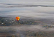 A hot air balloon glides over the early morning fog for of Cairns.