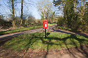 Red rural post box on its own at small road junction, Boulge, Suffolk, England