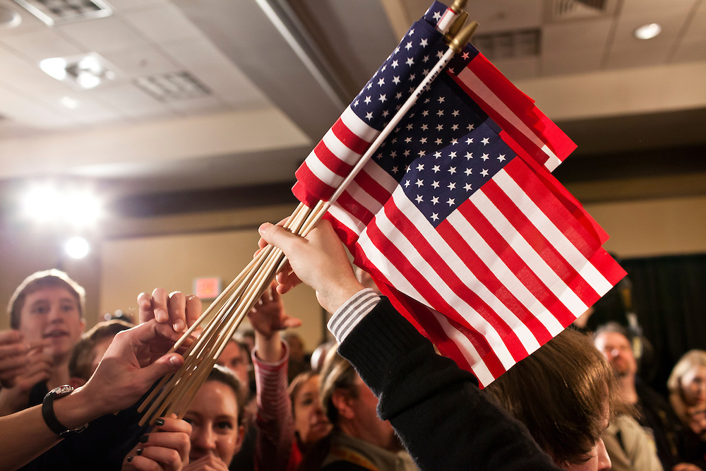 American flags are distributed at a caucus night rally for Republican presidential candidate Ron Paul on Tuesday, January 3, 2012 in Ankeny, IA.