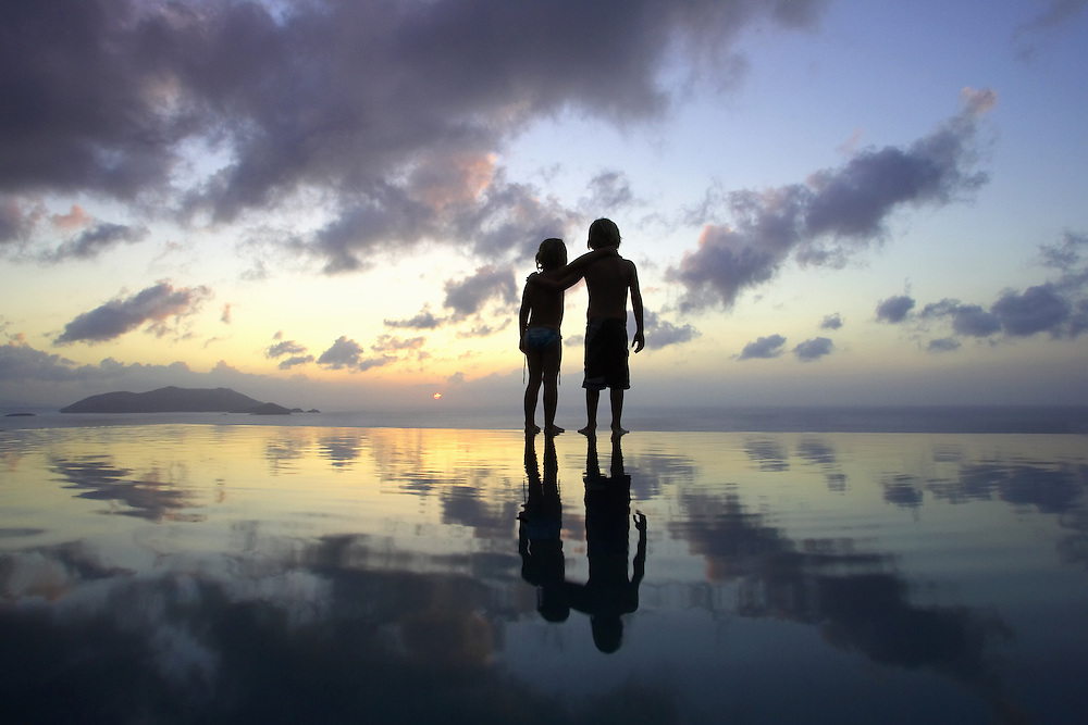 Infinity pool reflection of kids watching the sunset over the British Virgin Islands