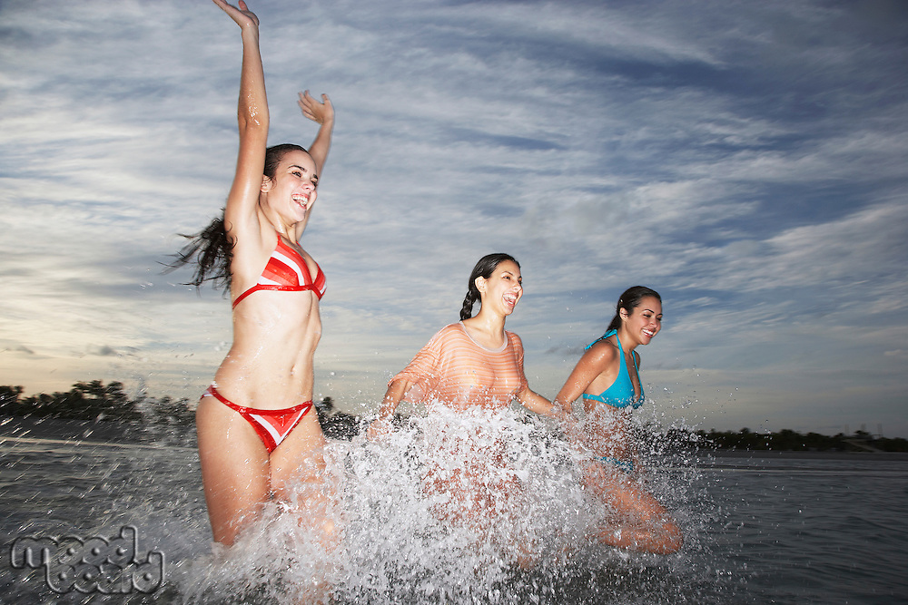 Three teenage girls (17-19) splashing in sea