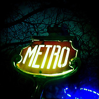 "Illuminated Paris Subway Sign ""Metro"" against a dark night sky"