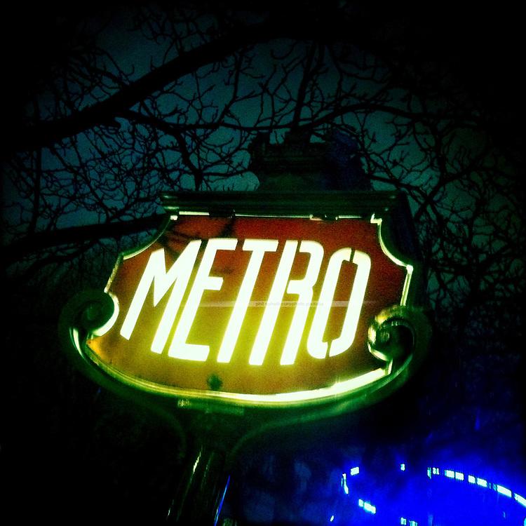 """Illuminated Paris Subway Sign """"Metro"""" against a dark night sky"""