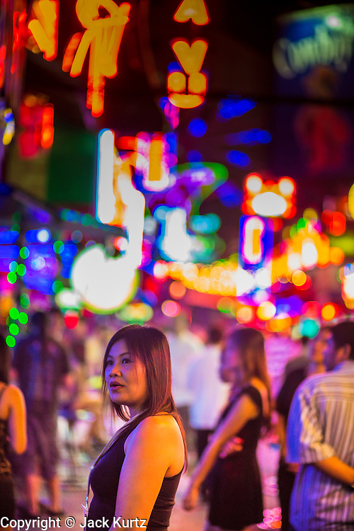 "19 JANUARY 2013 - BANGKOK, THAILAND:  A woman who works as a tout tries to draw men into a bar on Soi Cowboy, a red light district in Bangkok.  Prostitution in Thailand is technically illegal, although in practice it is tolerated and partly regulated. Prostitution is practiced openly throughout the country. The number of prostitutes is difficult to determine, estimates vary widely. Since the Vietnam War, Thailand has gained international notoriety among travelers from many countries as a sex tourism destination. One estimate published in 2003 placed the trade at US$ 4.3 billion per year or about three percent of the Thai economy. It has been suggested that at least 10% of tourist dollars may be spent on the sex trade. According to a 2001 report by the World Health Organisation: ""There are between 150,000 and 200,000 sex workers (in Thailand).""       PHOTO BY JACK KURTZ"