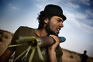 LIBYAN ARAB JAMAHIRIYA, Gualish : A Libyan rebel fighter carries a rocket at the front line near the southwest desert hamlet of Gualish as rebels repel an attack from forces loyal to Moamer Kadhafi aimed at capturing the city on July 24, 2011.ALESSIO ROMENZI