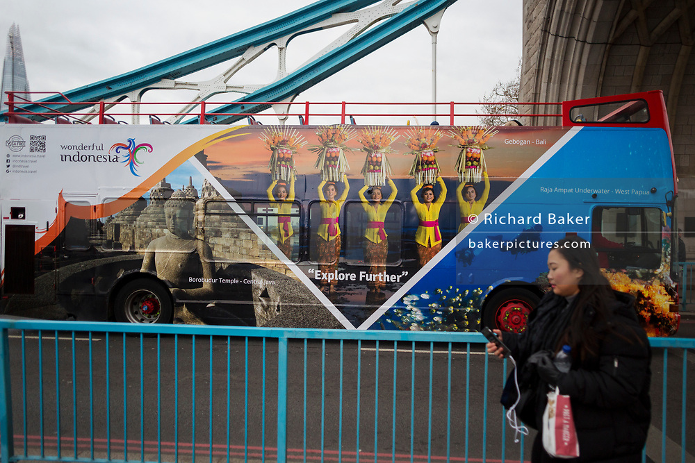 A London tour bus featuring a marketing ad campaign for the Indonesian tourist board crosses Tower Bridge, on 6th December 2017, in London England.