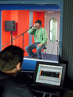 Young man singing in studio technician in foreground