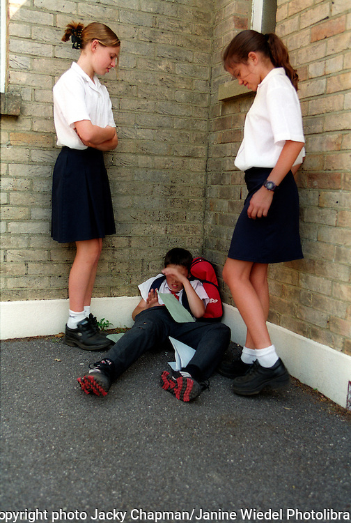 Girls bullying  a younger boy at school. posed by models
