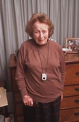 Elderly woman wearing personal alarm pendant around her neck,