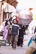 Workers in Marrakech carry their goods through the streets.