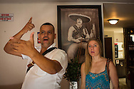 """30/03/2016 - Medellin, Colombia: Carlos Palau, a tour guide and former policeman, enacts the last day of Pablo Escobar for American tourist Elizabeth Wilky, 34, on Escobar's hideout in the Los Pinos neighbourhood, Medellin. The last residence of Pablo Escobar was transformed into  a brothel, but during the days allows tourists to visit the last place where the famous drug lord was hidden and later killed. Tours focusing on the life and death of Pablo Escobar are becoming quite popular among international tourists that visit Medellín. In recent times more than 10 tour operators have started to give the tour, helped by the interest generated by Netflix """"Narcos"""" series. (Eduardo Leal)"""