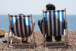© Licensed to London News Pictures. 03/05/2014. Brighton, UK. 2 people sit in a chair on Brighton beach while enjoying the sunshine. thousands of people are expected to come to Brighton for the May bank holiday weekend. Photo credit : Hugo Michiels
