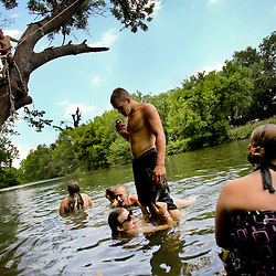 Kyle Green | The Roanoke Times<br /> June 28, 2010 A group of swimmers congregate near a pair of rope swings in the Roanoke River off of East Riverside Drive in Salem, Virginia.