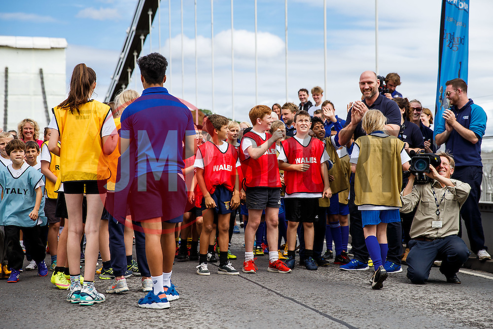 England World Cup Winner Lawrence Dallaglio congratulates a girl after she steps up and kicks the ball as Local Junior Schools take part in activities on the iconic Clifton Suspension Bridge with Bristol Rugby Players - Mandatory byline: Rogan Thomson/JMP - 07966 386802 - 14/07/2015 - SPORT - RUGBY UNION - Bristol, England - Clifton Suspension Bridge - Webb Ellis Cup visits Bristol as part of the 2015 Rugby World Cup Trophy Tour