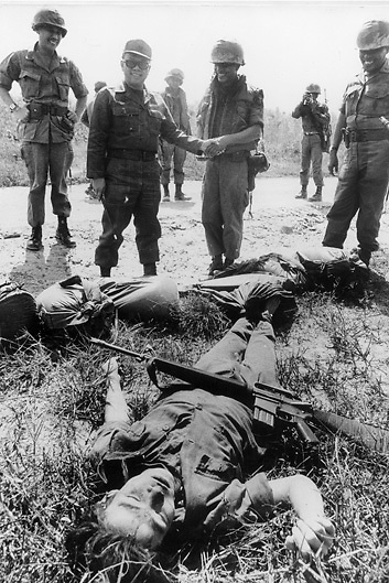 Thai general congratulates Thai troops on killing a suspected Viet Cong soldier in Vietnam during the Vietnam War