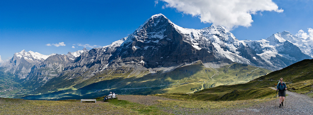 """Walk between Kleine Scheidegg and Männlichen to see sweeping views of Grindelwald Valley, Wetterhorn (far left), Eiger (middle), Mönch, and Jungfrau (right) in the Berner Oberland, Switzerland, the Alps, Europe. The world's longest continuous rack and pinion railway (Wengernalpbahn) goes from Grindelwald up to Kleine Scheidegg and down to Wengen and Lauterbrunnen. From Kleine Scheidegg, another cog train (Jungfraubahn) ascends steeply inside the Eiger to Jungfraujoch, the highest railway station in Europe. A gondola (gondelbahn) connects Grindelwald with Männlichen, where a cable car goes down to Wengen (Luftseilbahn Wengen-Männlichen). The Bernese Highlands are the upper part of Bern Canton. UNESCO lists """"Swiss Alps Jungfrau-Aletsch"""" as a World Heritage Area (2001, 2007). Panorama stitched from four images."""