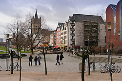 """Cologne, Germany, Jan. 2012 - Pedestrians walk along the Rhein river promenade in the """"Old Town"""" district, in Cologne, Germany. The spire of Great St. Martin's church is seen in the background. (Photo © Jock Fistick)."""