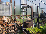 Sill-life of firewood and heater in the greenhouse at Harmony Farm, Goshen, NY.
