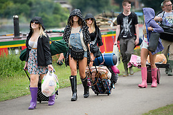 © London News Pictures. 22/08/2013. Reading, UK. Festival goers walk along the banks of the River Themes in Reading, Berkshire as they arrive at Reading Festival on August 22, 2013. The three day event which attracts over 80,000 music revellers  opens officially tomorrow (Friday) and will headline the likes of EMINEM, Green Day and Biffy Clyro. Photo credit: Ben Cawthra/LNP