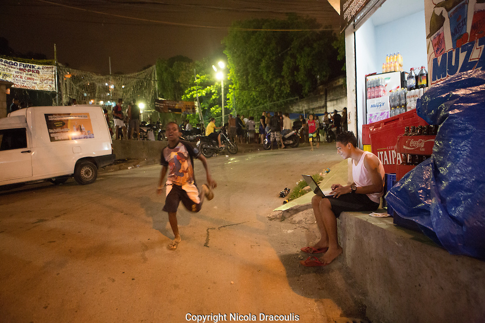 Boy on a laptop in the street next to a Baile Funk party, Casinhas, Complexo do Alemao, Brazil
