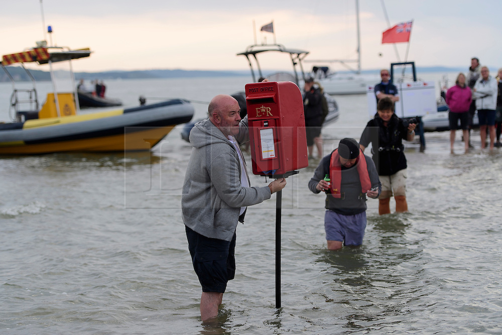 © Licensed to London News Pictures. 18/09/2016. Portsmouth, UK. A royal mail post box being put up in the middle of the sea.  Teams take part in the  Bramble Bank Cricket Match in the middle of The Solent strait on September 18, 2016. The annual cricket match between the Royal Southern Yacht Club and The Island Sailing Club, takes place on a sandbank which appears for 30 minutes at lowest tide. The game lasts until the tide returns. Photo credit: Ben Cawthra/LNP